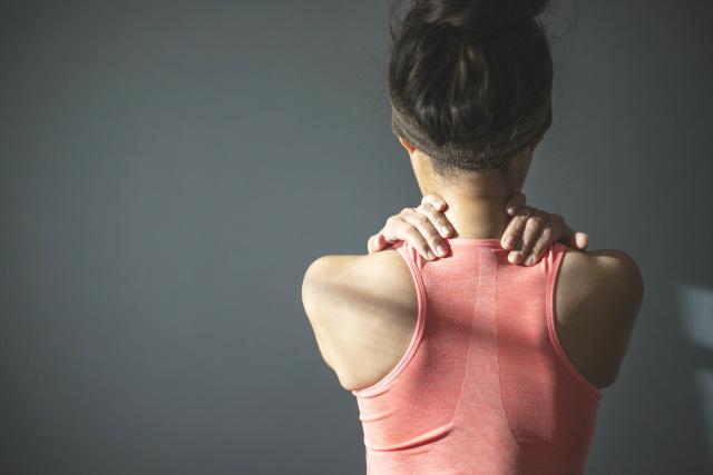 オーバーワークで首から肩にかけて凝っている女性