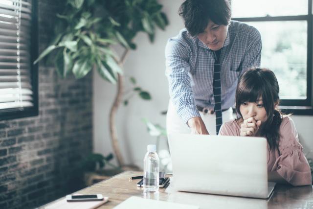 後輩の女性社員に仕事を教える男性社員